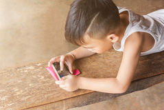 Little Asian boy playing game via mobile or cellphone Royalty Free Stock Photos