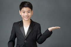 Little asian boy pointing to space at right with palm up Royalty Free Stock Photos