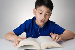 Little asian boy read a book Stock Images