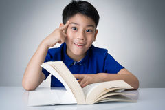 Little asian boy read a book and think about Royalty Free Stock Image