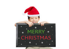 Little Asian boy in red Santa hat  holding chalkboard with Merry Royalty Free Stock Photography