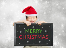 Little Asian boy in red Santa hat  holding chalkboard with Merry Royalty Free Stock Photo