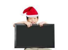 Little Asian boy in red Santa hat  holding chalkboard Stock Photos