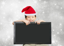Little Asian boy in red Santa hat  holding chalkboard Royalty Free Stock Photos