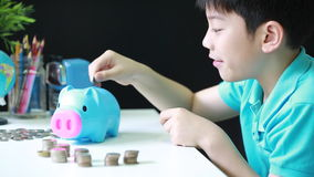 Little asian boy saving money in to piggy bank stock video footage