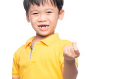 Little asian boy showing his lost milk-tooth in his hand - close. Up Stock Photography