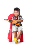 Little asian boy sits on a chair with a guitar Stock Photos