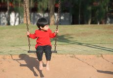 Little boy sitting and looking on hanging seat swing. Little asian boy sitting and looking on hanging seat swing Royalty Free Stock Photography