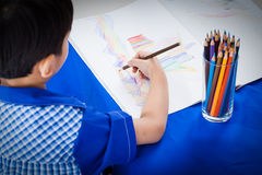 Little asian boy sitting at the table and drawing Royalty Free Stock Photo