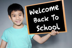 Little asian boy smiles holding wood black board  With Back to S Royalty Free Stock Photo