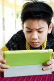 Little asian boy smiles with tablet computer acting on his face Stock Image