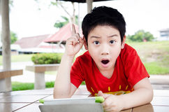 Little asian boy smiles with tablet computer Stock Photography