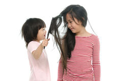Little asian boy smiling and brushing sister hair Stock Image