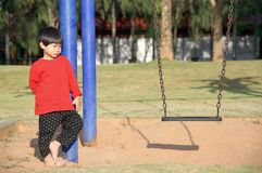 Little boy standing and looking the hanging seat swing. Little asian boy standing and looking the hanging seat swing Royalty Free Stock Photos