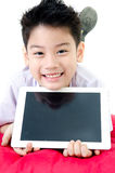Little asian boy in student's uniform with tablet computer on is Stock Image