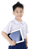 Little asian boy in student's uniform with tablet computer on is Stock Photos