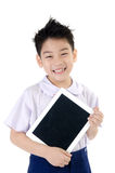 Little asian boy in student's uniform with tablet computer on is Royalty Free Stock Images