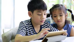 Little asian boy with tablet computer and little girl playing together stock video