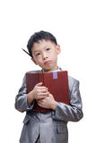 Little Asian boy thinking in suit standing with a diary Royalty Free Stock Image