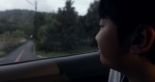 Little asian boy travelling in car and looking through the window stock video footage