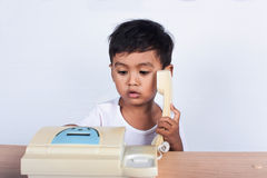 A little asian boy use telephone Stock Image