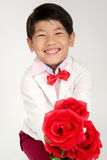 Little Asian boy in vintage suit with red rose Stock Images