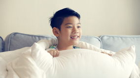 Little Asian boy watching TV on sofa stock footage