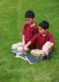 Little asian boys with books. Two cute asian boys reading in grass royalty free stock photo