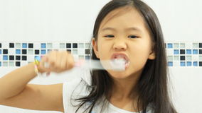 Little Asian child brushing her teeth