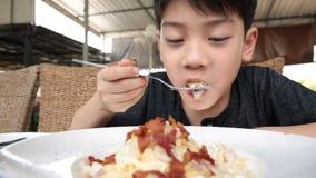 Little asian child eating pasta at restaurant . stock video