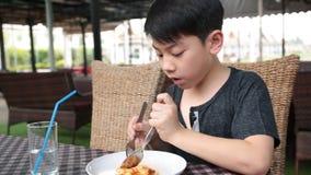 Little asian child eating pizza at restaurant . stock video