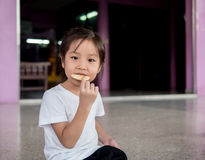 Little asian  child girl eating a cookie Stock Photos