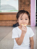 Little asian  child girl eating a cookie Royalty Free Stock Photo