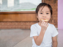 Little asian  child girl eating a cookie Stock Photography