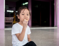 Little asian  child girl eating a cookie Royalty Free Stock Images