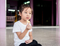 Little asian  child girl eating a cookie Royalty Free Stock Photos