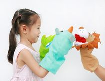 Little Asian child girl hands playing animal puppets with hand of her mother on white background. Educations concept royalty free stock photo