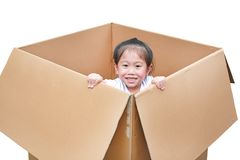 Little Asian child girl playing peekaboo and lie in big cardboard box isolated on white background.  stock photo