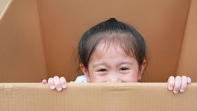 Little Asian child girl playing peekaboo and lie in big cardboard box.  stock photography