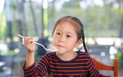 Little Asian child girl sitting at the cafe and eating food with looking straight at camera.  stock photography