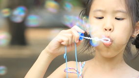 Little Asian child having fun making bubbles