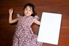 Little Asian child laying down on the wooden background with a b Stock Photo