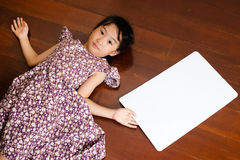 Little Asian child laying down on the wooden background with a b Stock Photos