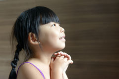 Little Asian child looking up. Little Asian girl looking up and with her fingers closed Stock Photography