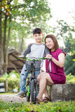 Little Asian child with mother practice to riding a bicycle Royalty Free Stock Images