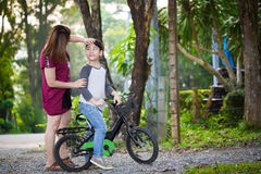 Little Asian child with mother practice to riding a bicycle Stock Image