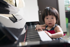 Little Asian child at piano Stock Image