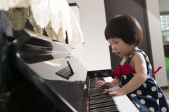 Little Asian child at piano stock images