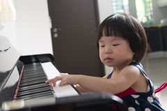 Little Asian child at piano Stock Photography