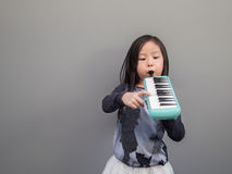Little asian child play the melodion Royalty Free Stock Image